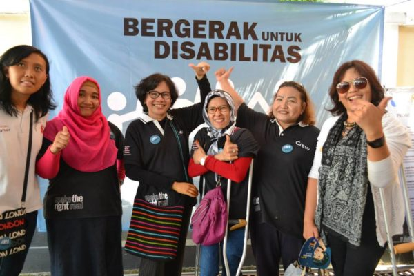 Women in Indonesia stand in front of sign, unity