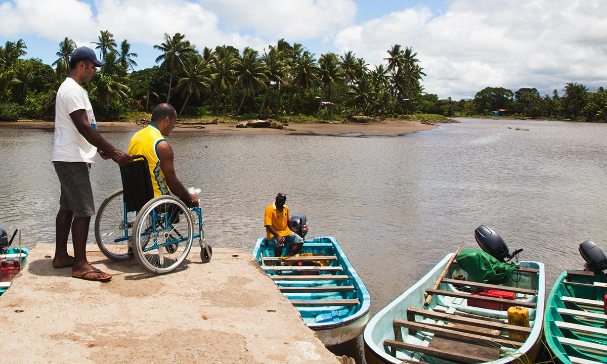 man using wheelchair with man next to him looks to get on to row boat