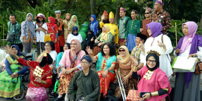 Gathering of persons with disabilities in Indonesian traditional dress
