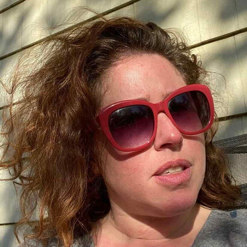Image of Alice Phinizy, woman with curly hair wearing red sunglasses
